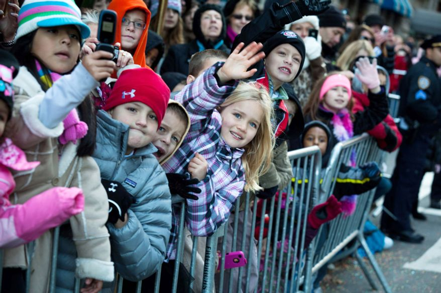 Young spectators wave to Santa Claus as he rolls down 7th Avenue during the Macy's Thanksgiving Day Parade. (AP Photo/John Minchillo)