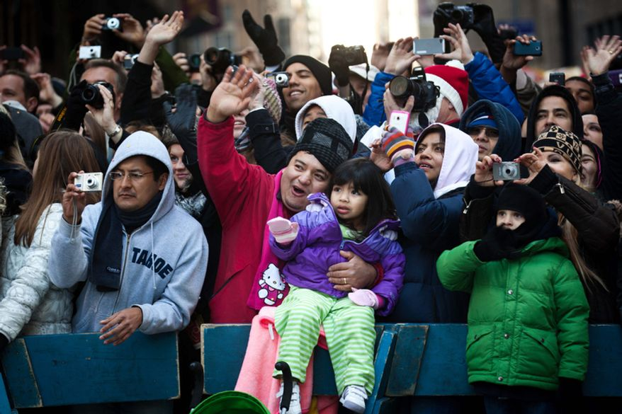 Spectators wave and aim their cameras at Santa Claus as he rolls down 7th Avenue during the Macy's Thanksgiving Day Parade. (AP Photo/John Minchillo)