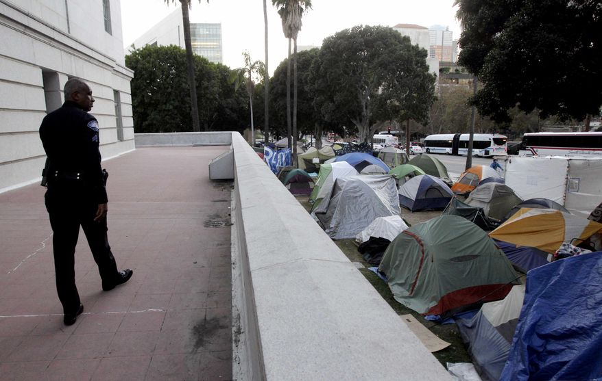 ** FILE ** In this Nov. 2, 2011, photo, a Los Angeles police officer looks at tents set up outside Los Angeles City Hall in Los Angeles. The Occupy Los Angeles encampment around City Hall will be cleared sometime next week, a city official and a lawyer for demonstrators said Wednesday, Nov. 23, 2011. (AP Photo/Jae C. Hong)