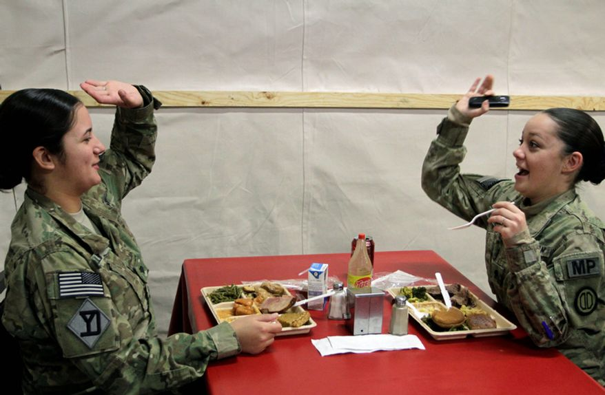 U.S. soldiers react, as they eat lunch meal to mark Thanksgiving Day at the U.S. base Camp Eggers in Kabul, Afghanistan, Thursday, Nov. 24, 2011. (AP Photo/Musadeq Sadeq)