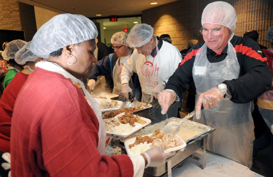 Atlanta Falcons NFL head football coach Mike Smith, right, and owner Arthur Blank serve food at Hosea Feed the Hungry and Homeless on Thursday, Nov. 24, 2011, at the Georgia World Congress Center in Atlanta. Smith's Thanksgiving was an event-filled day that included practice, some community service and family time. (AP Photo/Erik S. Lesser)
