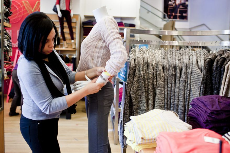 Wanda King, of Hyattsville, Md., attaches a mannequin's hand at the Gap's Georgetown store as shops open for business on Thanksgiving day in Washington, D.C. on Nov. 24, 2011.(T.J. Kirkpatrick/ The Washington Times)