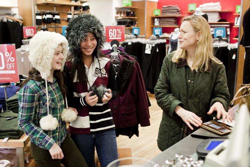 Gina Youngman, right, of New Canaan, Conn., reacts as her daughter Sarah, 15, from left, and friend Celina Sprague, of Washington, D.C., model hats at the Gap's Georgetown store on Thanksgiving day in Washington, D.C. on Nov. 24, 2011.(T.J. Kirkpatrick/ The Washington Times)