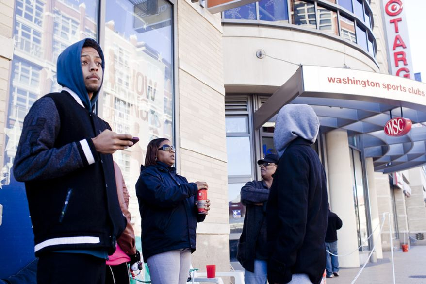 Mason Binion, of Washington, D.C., at left and Tasha Johnson, of Washington, center, wait in line with other shoppers along 14th Street NW for the midnight opening at the DC USA Shopping Center in Columbia Heights on Thanksgiving day in Washington, D.C. on Nov. 24, 2011.