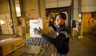 **FILE** An Amazon.com employee grabs boxes to load onto a truck at the company's Fernley, Nev., warehouse. (Associated Press)