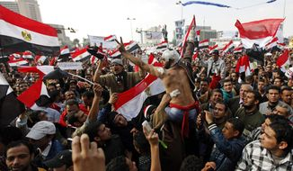 Protesters, including a wounded man, chant slogans and wave Egyptian national flags during a rally in Tahrir Square in Cairo on Nov. 25, 2011. (Associated Press)