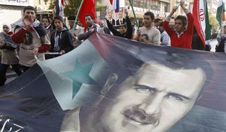 Pro-Syrian regime protesters shout slogans and carry a huge portrait of Syrian president Bashar Assad during a protest against the Arab League decisions in Damascus, Syria, on Nov. 25, 2011. Syria missed an Arab League deadline to allow hundreds of observers into the country, prompting the bloc to consider economic sanctions against Damascus for its eight-month crackdown on dissent, a senior diplomat said. (Associated Press)