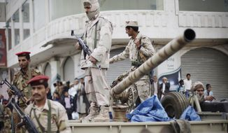 Defected army soldiers stand guard on a vehicle while protesters march during a demonstration demanding the prosecution of Yemen President Ali Abdullah Saleh in Sanaa, Yemen, on Nov. 24, 2011. (Associated Press)