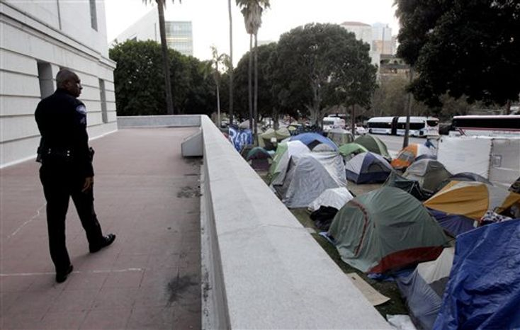 FILE - In this Nov. 2, 2011 file photo, a Los Angeles police officer looks at tents set up outside Los Angeles City Hall in Los Angeles. Occupy LA, a 485-tent camp surrounding City Hall downtown, has marched to a different beat in its drum circle. Protesters, police and city officials early on established a relationship based on dialogue instead of dictate. As camps in other cities degenerated into unrest and led to mass arrests, Occupy LA has remained largely a bastion of peaceful pot smokers with city leaders determined that Los Angeles would emerge from the shadow of Rodney King once and for all. (AP Photo/Jae C. Hong, File)