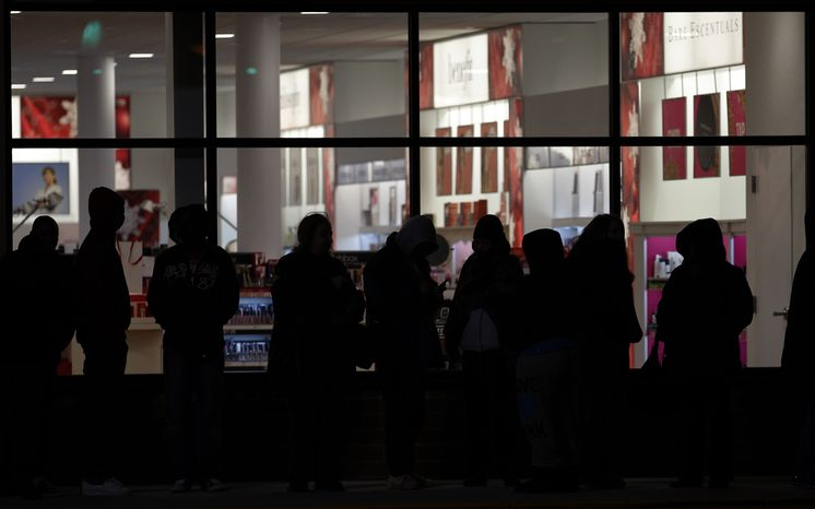 Early bird shoppers wait in a long line to get into the midnight opening of an Old Navy store in Mayfield Heights, Ohio, on Thursday, Nov. 24, 2011. (AP Photo/Amy Sancetta)