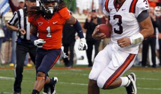 Virginia Tech quarterback Logan Thomas walks in for a touchdown as Virginia cornerback Demetrious Nicholson follows during the first half at Scott Stadium in Charlottesville, Va., Saturday, Nov. 26, 2011. (AP Photo/Steve Helber)