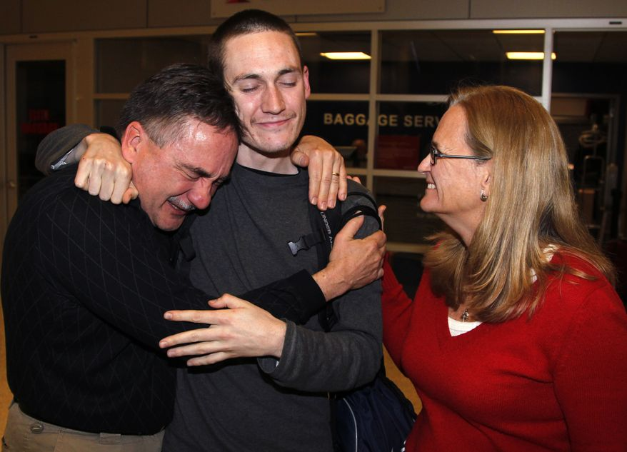 Luke Gates (center), 21, gets a hug from his parents, Bill (left) and Sharon Gates, on Sunday, Nov. 27, 2011, after arriving at Indianapolis International Airport in Indianapolis. (AP Photo/Michael Conroy)