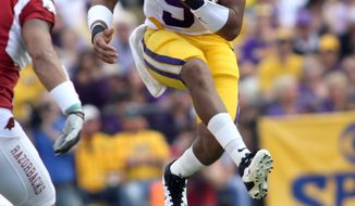 LSU quarterback Jordan Jefferson hurdles another player as he runs with the ball against Arkansas during the game in Baton Rouge, Friday, Nov. 25, 2011. LSU defeated Arkansas 41-17. (AP Photo/The Lafayette Daily Advertiser, Leslie Westbrook)