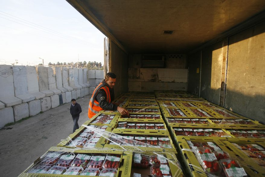 A Palestinian customs worker checks a truck loaded with boxes of strawberries at the Kerem Shalom crossing between the Gaza Strip and Israel on Sunday, Nov. 27, 2011. Farmers in Gaza began exporting tons of produce to Europe on Sunday after Israel cracked open the volatile border. (AP Photo/Eyad Baba)
