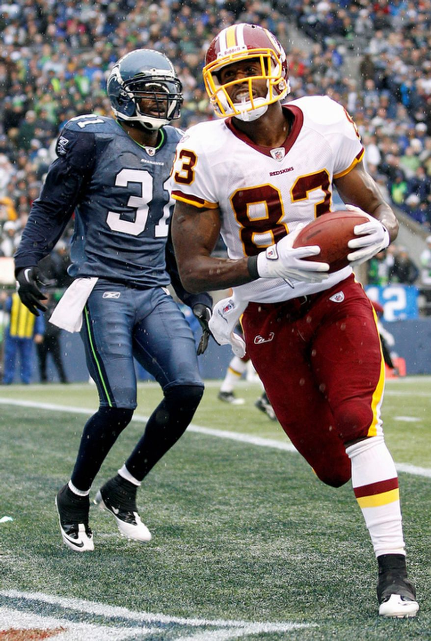 Washington Redskins' Fred Davis, right, runs past Seattle Seahawks' Kam Chancellor, left, after catching a pass for a touchdown in the first quarter of an NFL football game. (AP Photo/Ted S. Warren)