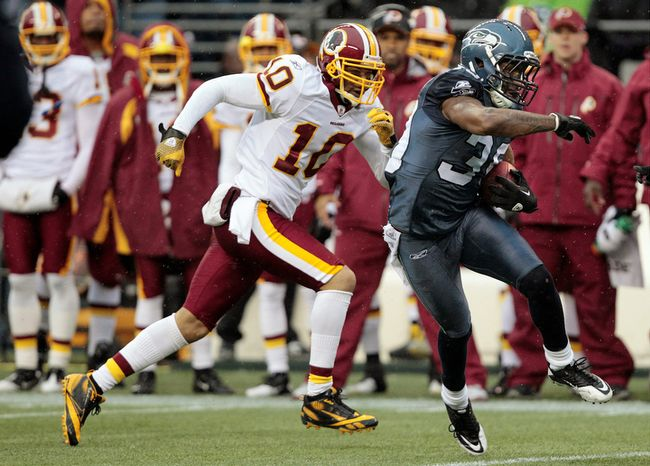 Seattle Seahawks' Brandon Browner, right, runs with ball after intercepting a pass intended for Washington Redskins' Jabar Gaffney, left, in the first half of an NFL football game. (AP Photo/Elaine Thompson)