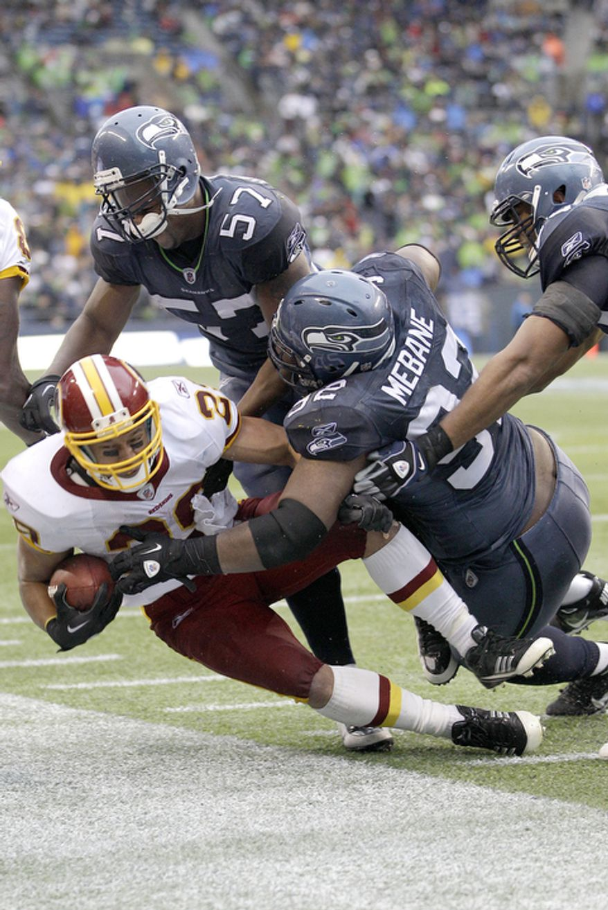 Washington Redskins Roy Helu is tackled by David Hawthorne (57) and Brandon Mebane (92) in the first half. (AP Photo/Ted S. Warren)