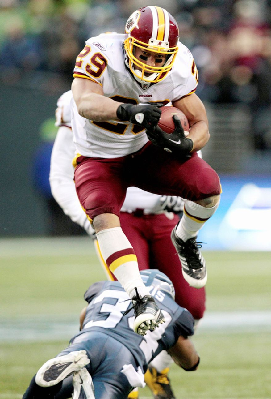 Washington Redskins' Roy Helu leaps over Seattle Seahawks' Roy Lewis on his way to a touchdown in the second half. (AP Photo/Elaine Thompson)