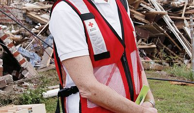 ** FILE ** Red Cross Director Gail McGovern stands next to the remains of a destroyed house in Pratt City, Ala., on Sunday, May 1, 2011. Ms. McGovern says the 130-year-old Red Cross had little choice but to restructure in order to ward off a projected deficit. (AP Photo/Butch Dill, File)