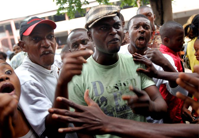Voters argue with election officials over the delayed opening Monday of a polling place in Kinshasa, the capital city of Congo. Residents waited to take part in presidential and legislative elections. (Associated Press)