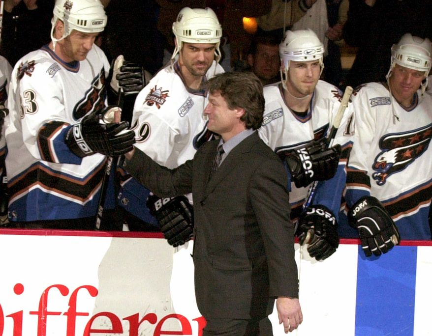 ** FILE ** Dale Hunter is congratulated by former Washington Capitals teammates (from left) Jim McKenzie, Joe Reekie, Brendan Witt and Calle Johansson during a ceremony to retire Hunter's number before the team's game with the New Jersey Devils in Washington on March 11, 2000. (AP Photo/Linda Spillers, File)