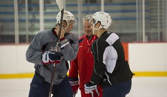 Washington Capitals Head Coach Dale Hunter (center) chats with Alexander Semin (left) and Dmitry Orlov (right) as he takes to the ice for the first time, at the Kettler Capitals Iceplex in Arlington, Va, Monday, Nov. 28, 2011. Semin was scratched Saturday, Dec. 3, 2011, against the Ottawa Senators with a shoulder injury. (Rod Lamkey Jr/ The Washington Times)