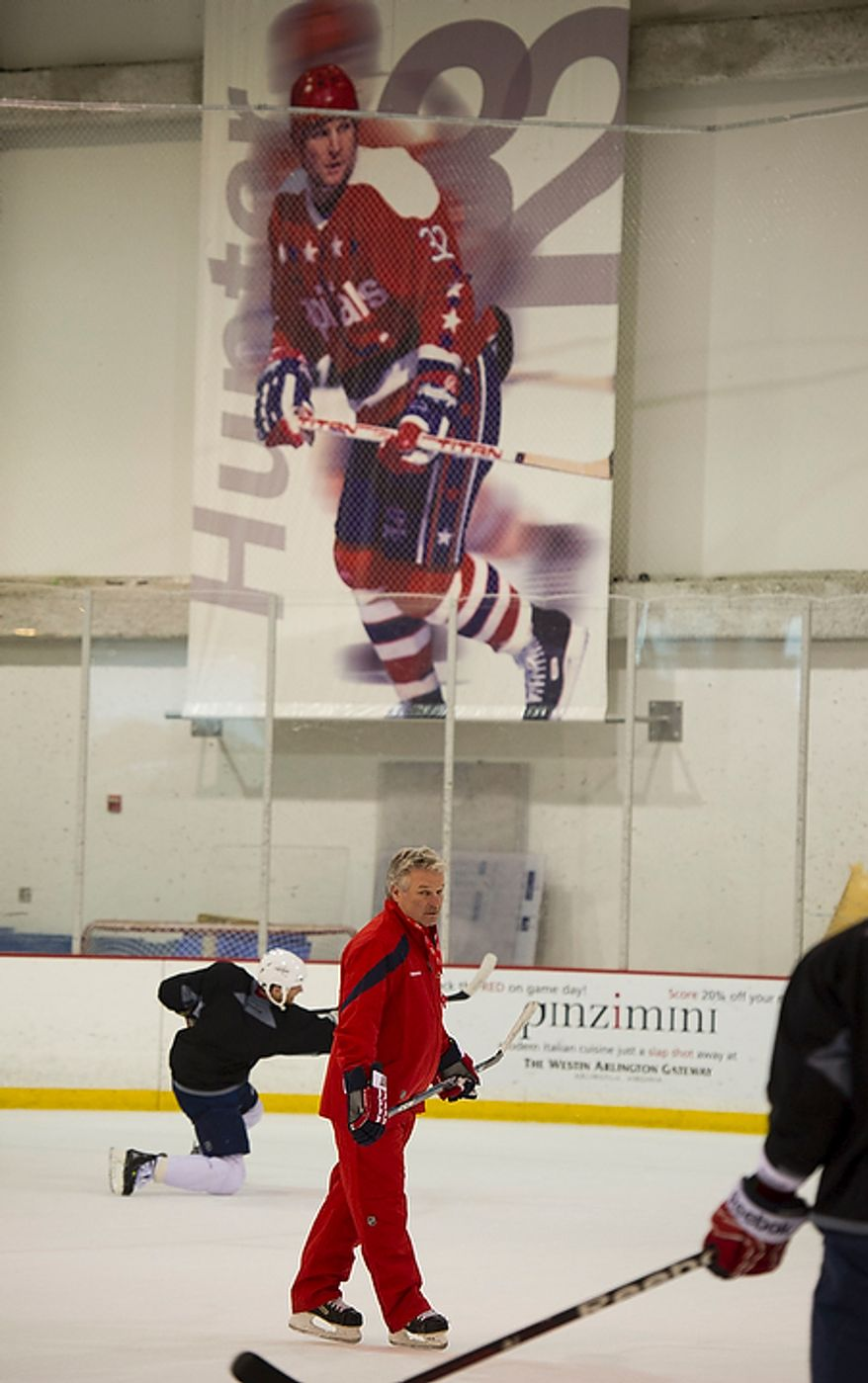 New Washington Capitals Head Coach Dale Hunter skates by a poster of himself when he was a player with the Capitals, as he takes to the ice with his team as they practice together for the first time, at the Kettler Capitals Iceplex in Arlington, Va, Monday, November 28, 2011. (Rod Lamkey Jr/ The Washington Times)