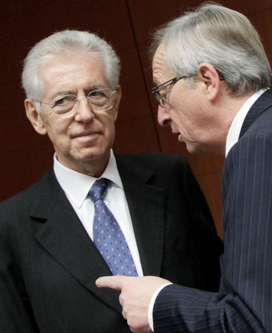 Luxembourg's prime minister, Jean-Claude Juncker (right), speaks with Italian Prime Minister and Finance Minister Mario Monti at the EU Council building in Brussels. The 17 finance ministers of euro-using countries met Tuesday in a bid to save their currency and to protect the rest of the global economy from a debt-induced financial tsunami. (Associated Press)