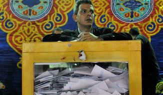 """An Egyptian election official waits for the opening of ballot boxes at a vote-counting center in Cairo on Tuesday. """"These elections are completely different from anything we've had before,"""" said taxi driver Mohammed Farouk. (Associated Press)"""