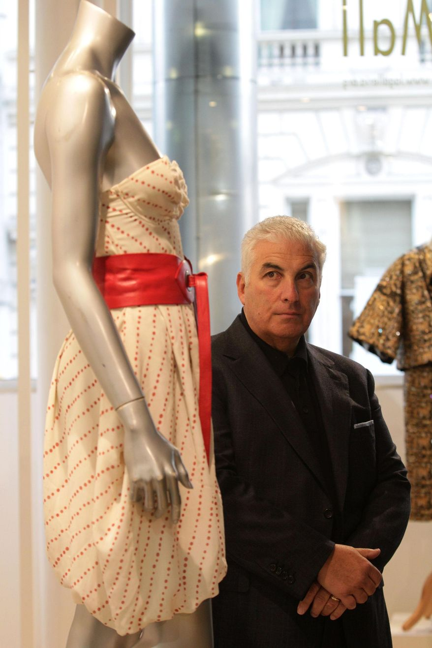 """Mitch Winehouse gazes at his late daughter Amy Winehouse's chiffon dress that fetched $67,120 at the """"Passion for Fashion"""" auction in London. (Associated Press)"""