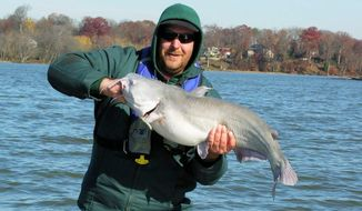 George Edens, of Mount Airy, Md., shows off a medium-size blue catfish caught near Fort Washington Light. Fort Washington is run by the National Park Service. (Gene Mueller/The Washington Times)