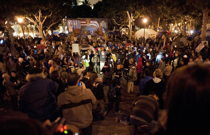A crowd gathers during the Occupy L.A. protest in Los Angeles on Tuesday, Nov. 29, 2011. Officers began a raid on the camp early Wednesday, two days after a deadline passed for protesters to clear out. (AP Photo/Dan Steinberg)