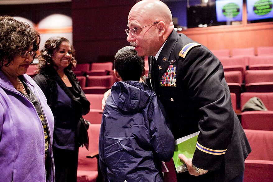 Mark Grapin, an Army National Guard chief warrant officer, right, hugs his son Eric, 11, as his mother-in-law Lena Christian, from left, and wife, Brinda, after a hearing before the Fairfax County Board of Zoning and Appeals in support of an ordinance that would allow him to keep a treehouse in his front yard, in Fairfax, Va., on Nov. 30, 2011. (T.J. Kirkpatrick/The Washington Times)