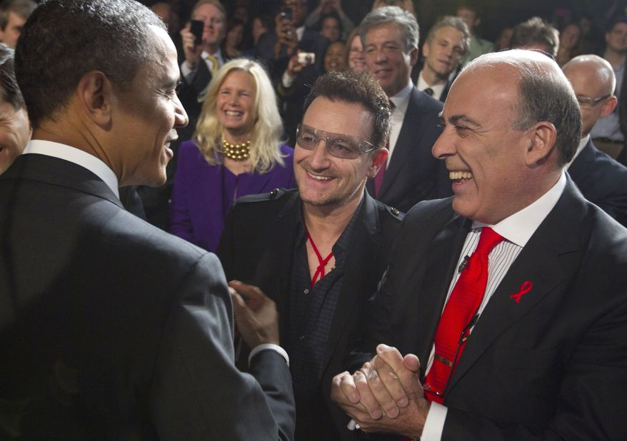 President Barack Obama greets U2 front man Bono, center, and Muhtar Kent, chairman of the Board and chief executive officer of The Coca-Cola Company, right, after speaking during a World AIDS Day event at George Washington University in Washington, Thursday, Dec. 1, 2011. (AP Photo/Carolyn Kaster)