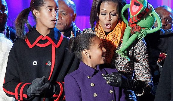 First lady Michelle Obama, with Kermit the frog, sings songs with daughters Malia, left, and Sasha Obama after the lighting of the National Christmas Tree at the Ellipse across from the White House in Washington, Thursday, Dec., 1, 2011. (AP Photo/Pablo Martinez Monsivais)