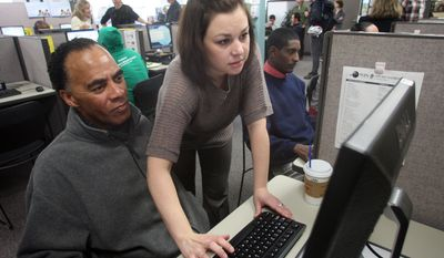 Maria Aplington of United Parcel Service helps Craig Wooten navigate the company's website during a hiring event for the firm at WorkSource Oregon on Wednesday, Nov. 3, 2011, in Portland, Ore. (AP Photo/Rick Bowmer)