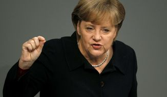 German Chancellor Angela Merkel gestures during her speech at the German Federal Parliament, Bundestag, in Berlin, Germany, Friday, Dec. 2, 2011. (AP Photo/Michael Sohn)