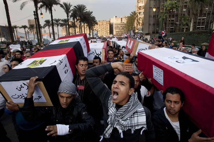 Protesters carry symbolic coffins honoring those killed in recent clashes with security forces during a rally in Tahrir Square, in Cairo, Egypt, Friday, Dec. 2, 2011. Islamists appear to have taken a strong majority of seats in the first round of Egypt's first parliamentary vote since Hosni Mubarak's ouster. (AP Photo/Bernat Armangue)