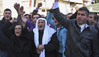 """In this photo taken during a government-organized tour for the media, relatives of Sari Saoud a 9-year-old boy who was shot dead in Homs three days ago while he was buying cookies from a shop, shout pro-Syrian regime and unity slogans, in the village of Kfarbo in Hama province, Syria, on Thursday, Dec. 1, 2011. Georgina the mother of Sari blamed """"armed terrorists"""" for killing her son. (AP Photo/Bassem Tellawi)"""