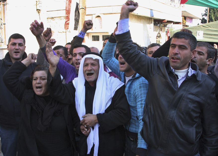 "In this photo taken during a government-organized tour for the media, relatives of Sari Saoud a 9-year-old boy who was shot dead in Homs three days ago while he was buying cookies from a shop, shout pro-Syrian regime and unity slogans, in the village of Kfarbo in Hama province, Syria, on Thursday, Dec. 1, 2011. Georgina the mother of Sari blamed ""armed terrorists"" for killing her son. (AP Photo/Bassem Tellawi)"