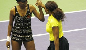 Venus Williams  and her sister, Serena, celebrate after winning a point during an exhibition doubles tennis match against Italy's Flavia Pennetta and Francesca Schiavone, in Milan, Italy, Saturday, Dec. 3, 2011. (AP Photo/Antonio Calanni)