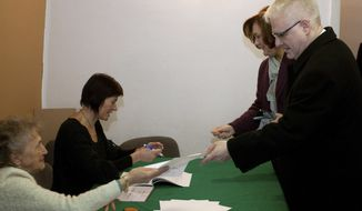 Croatian President Ivo Josipovic (right) receives his ballot at a polling station in Zagreb, Croatia's capital, on Sunday, Dec. 4, 2011. (AP Photo)