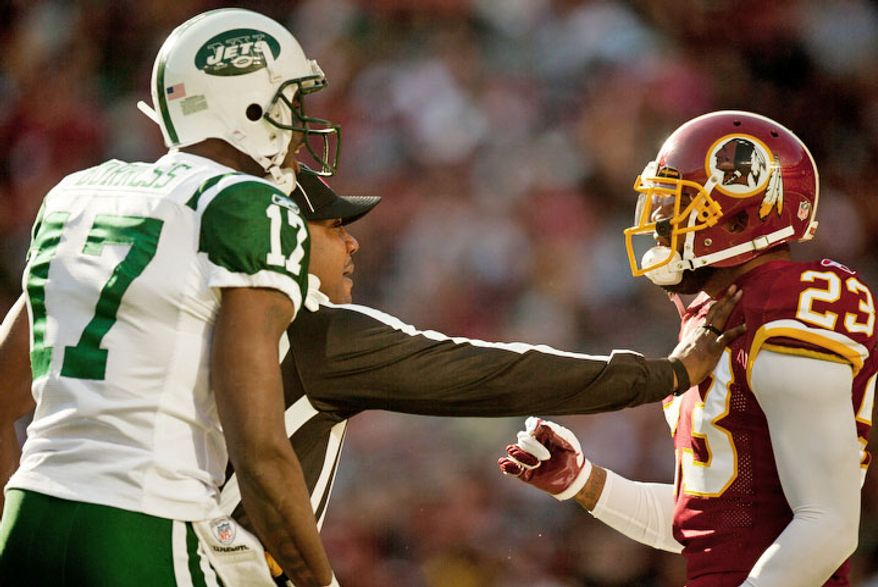 A referee separates Washington Redskins cornerback DeAngelo Hall (23) from New York Jets wide receiver Plaxico Burress (17) during the first quarter. (Pratik Shah/The Washington Times)
