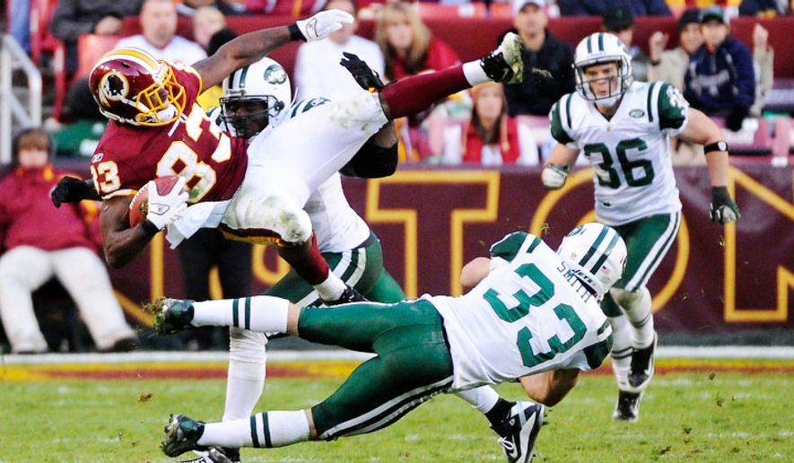 Washington Redskins tight end Fred Davis (83) is tackled by New York Jets outside linebacker Calvin Pace (back) and free safety Eric Smith (33) during fourth quarter. (Preston Keres/For The Washington Times)