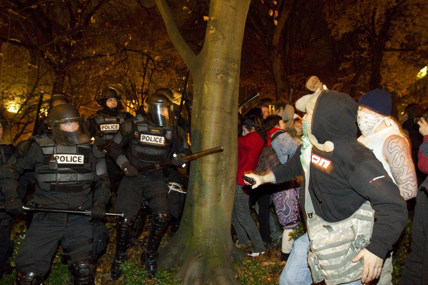 Riot police move into an area around a downtown Portland, Ore., park before arresting several anti-Wall Street protesters on Saturday night, Dec. 3, 2011, after the demonstrators refused to vacate the park. (AP Photo/Portland Oregonian, Randy L. Rasmussen)