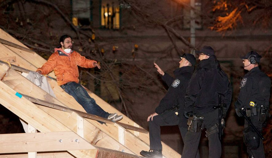 Park Police attempt to arrest protestors on the roof of a new structure the was erected in McPherson Square, in Washington, D.C. on Dec. 4, 2011.(T.J. Kirkpatrick/ The Washington Times)
