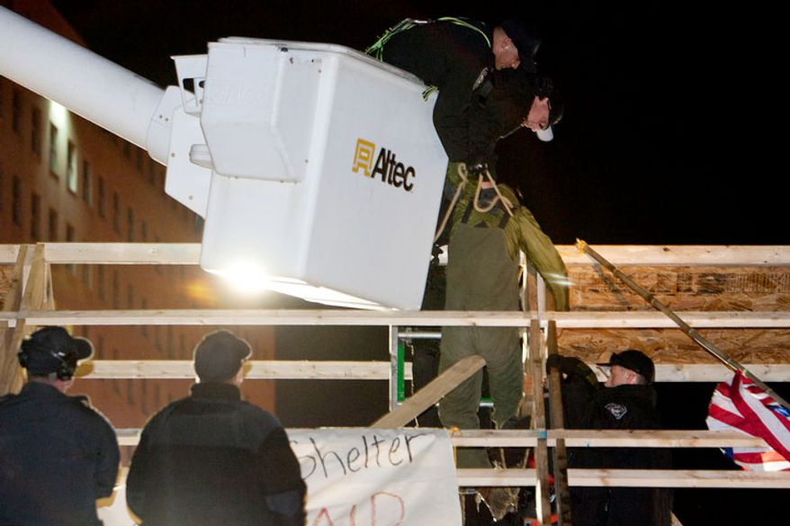 Park Police use a cherry picker to pull a protestor off the roof of a new structure the was erected in McPherson Square, in Washington, D.C. on Dec. 4, 2011.(T.J. Kirkpatrick/ The Washington Times)