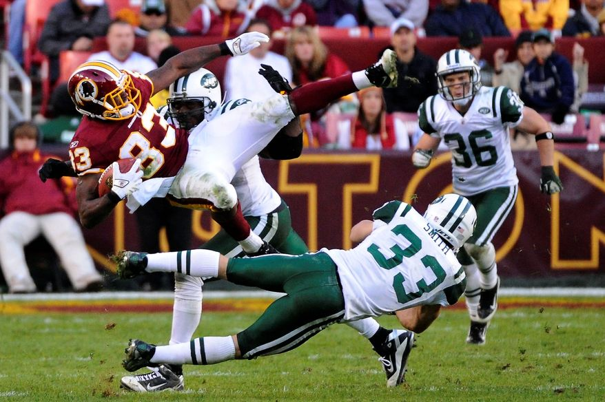 Washington Redskins tight end Fred Davis (83) is tackled by New York Jets outside linebacker Calvin Pace (back) and free safety Eric Smith (33) during fourth quarter action at FedEx Field in Landover, Md., on Sunday, December 4, 2011. (Preston Keres/For The Washington Times)