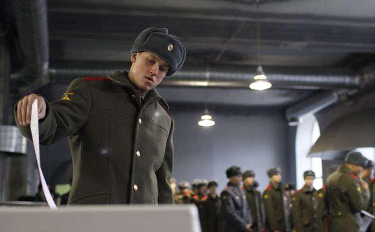 A Russian soldier casts his ballot as others stand in line at a polling station in Moscow on Sunday, Dec. 4, 2011.  (AP Photo/Alexander Zemlianichenko Jr.)