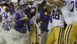 LSU head coach Les Miles is dowsed with water by guard Josh Williford and linebacker Seth Fruge during the second half of the Southeastern Conference championship game, Saturday, Dec. 3, 2011, in Atlanta. LSU won 42-10. (AP Photo/John Bazemore)